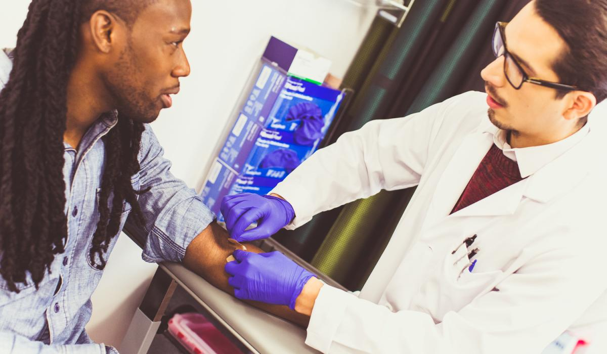 White male healthcare provider takes blood from arm of Black man