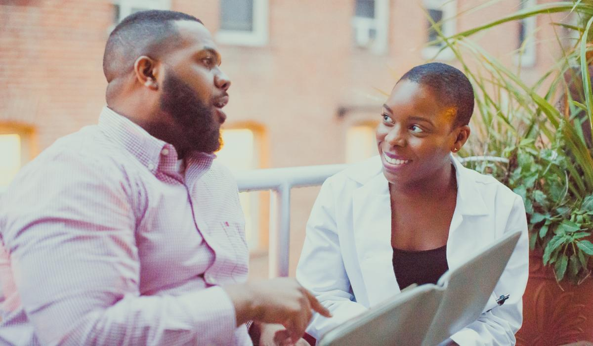 A Black male patient speaks to a Black female doctor