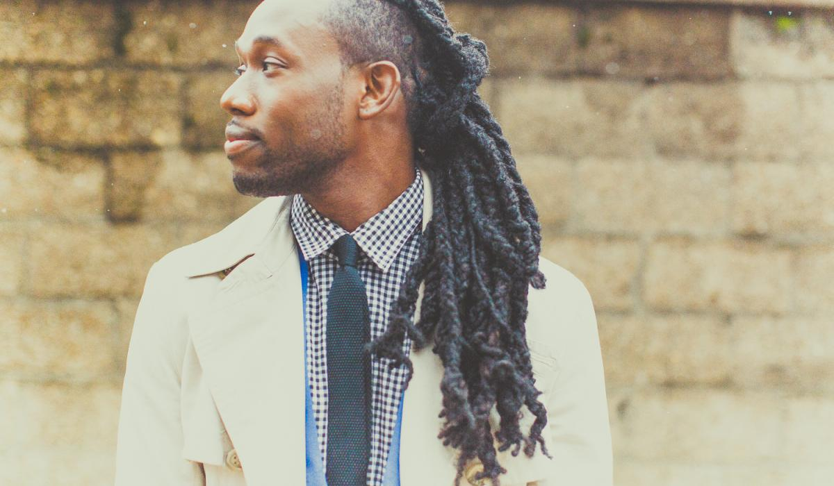 Black man with locs looking off screen