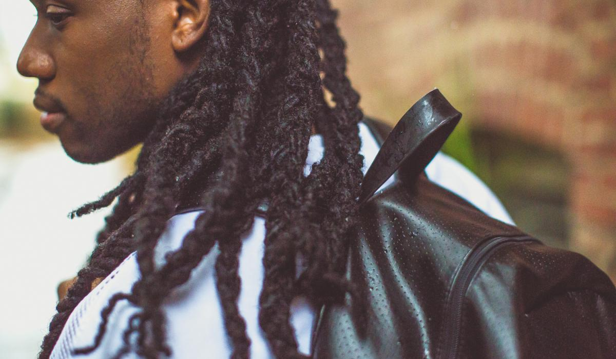 Young Black man with locs carries a backpack