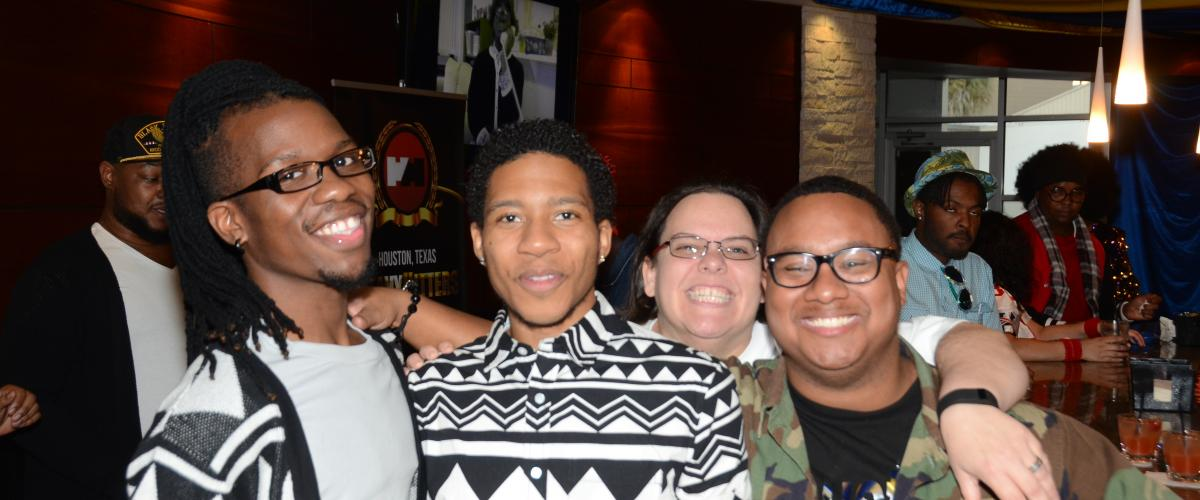 Three young Black men and a white woman smiling at the camera