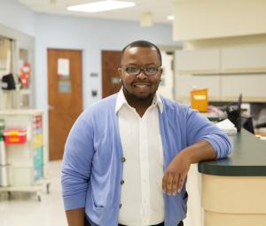 A Black man standing at a hospital desk